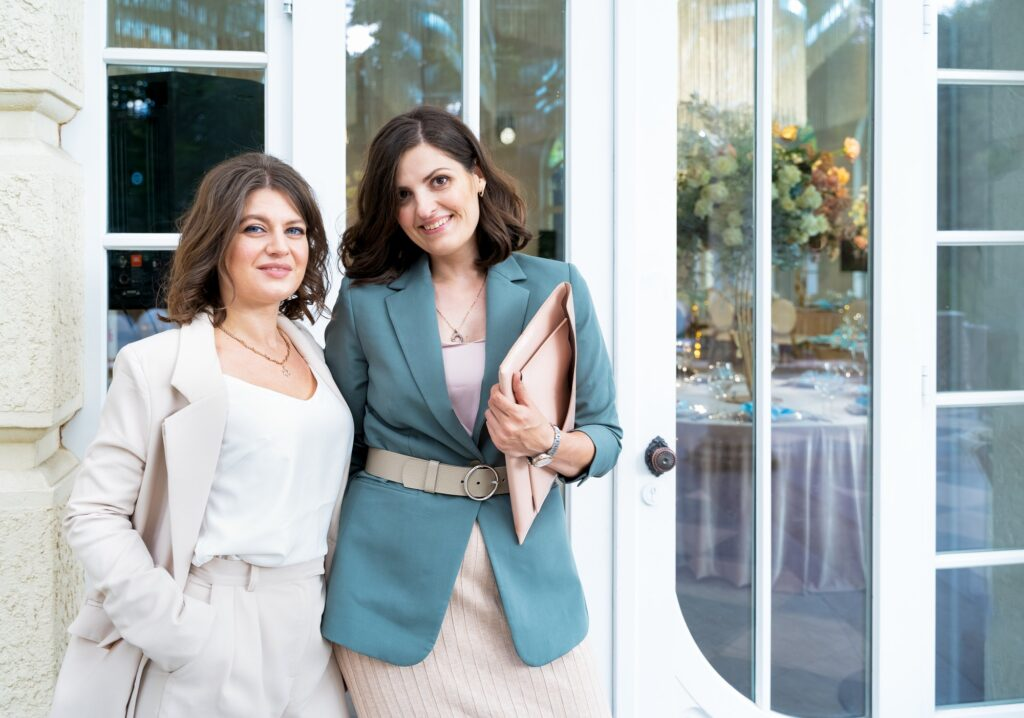Young beautiful women, girls in stylish suits at entrance to restaurant. Wedding organizers, event d